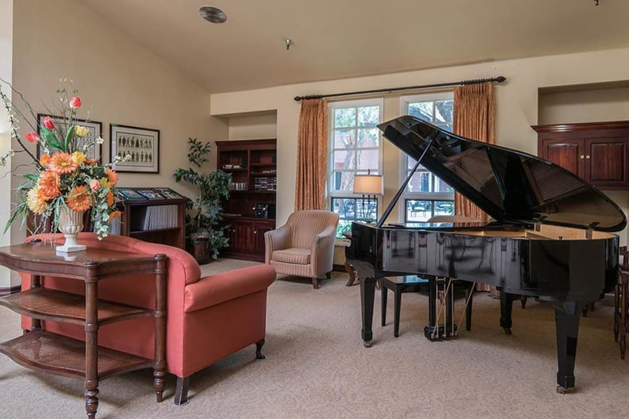 Grand piano with comfortable seating nearby in the lobby at Carmel Village in Fountain Valley, California