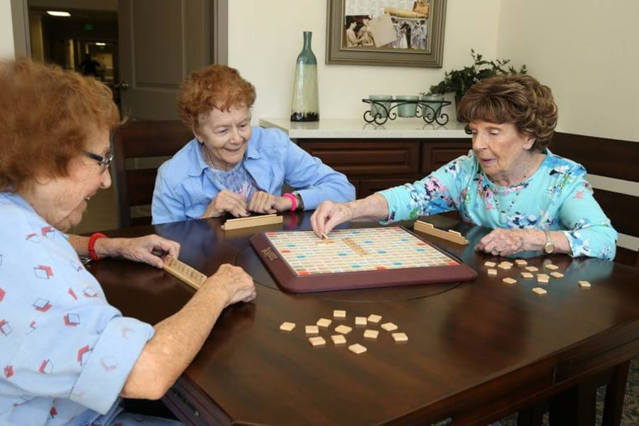Seniors enjoying a game of scrabble in community lounge at The Commons at Woodland Hills in Woodland Hills, California
