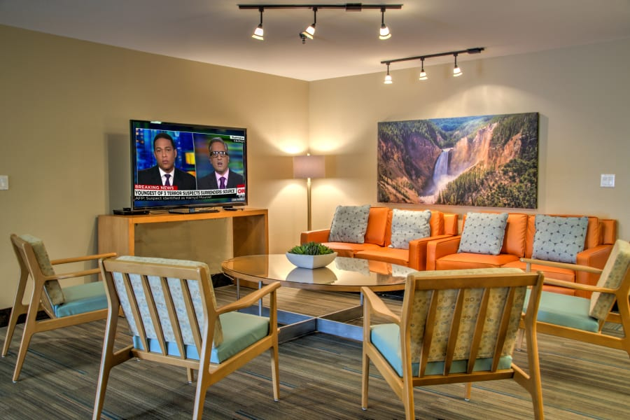 Flatscreen TVs and comfortable seating at one of the indoor common areas at Bella Vista Senior Living in Mesa, Arizona