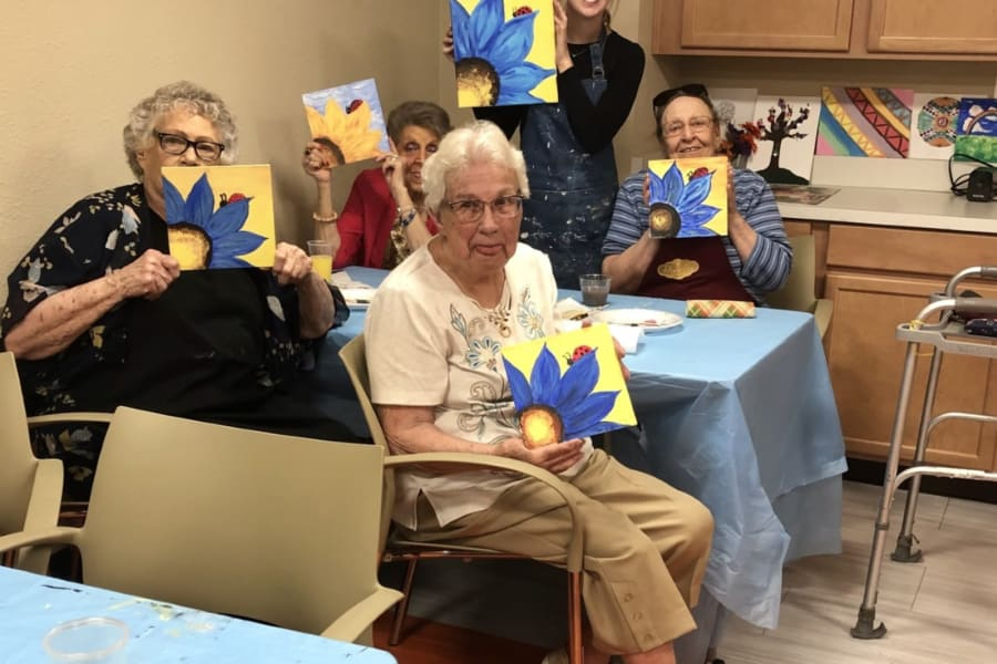 Residents proudly holding up their work for a photo at the acrylic painting and wine social at Bella Vista Senior Living in Mesa, Arizona