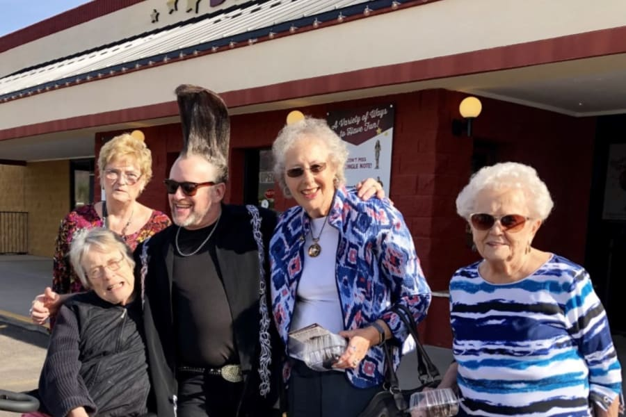 Residents posing with some of the act outside the Barleens Dinner Show outing from Bella Vista Senior Living in Mesa, Arizona