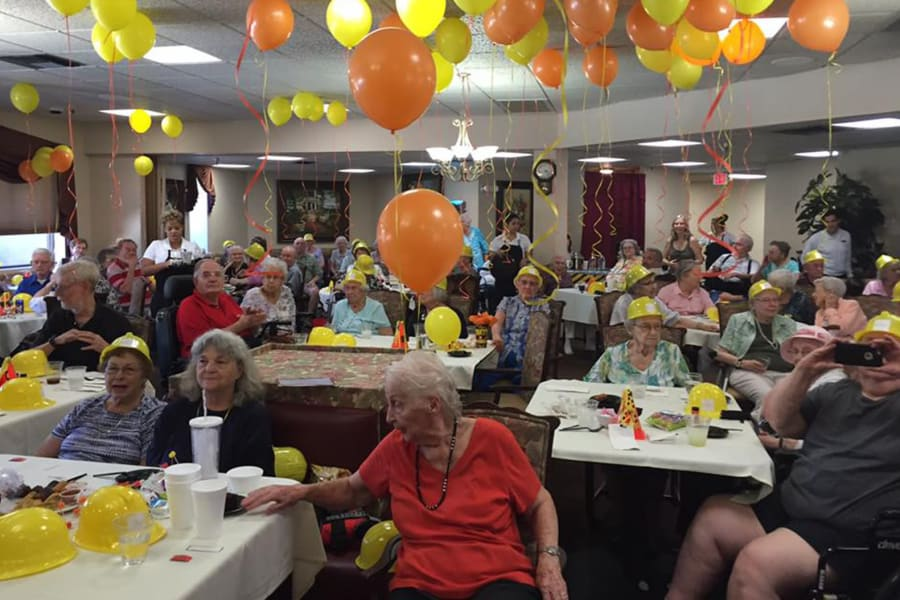Balloons on the ceiling and festive hats on heads at the dining room construction kick-off party at Bella Vista Senior Living in Mesa, Arizona