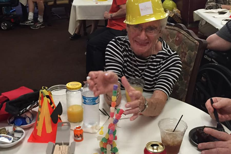 Happy resident telling a story at the dining room construction kick-off party at Bella Vista Senior Living in Mesa, Arizona