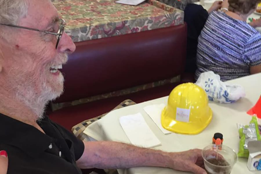 Resident smiling and talking with friends at the dining room construction kick-off party at Bella Vista Senior Living in Mesa, Arizona
