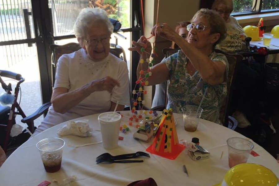 Ladies playing creating a toothpick and gumdrop masterpiece at the dining room construction kick-off party at Bella Vista Senior Living in Mesa, Arizona