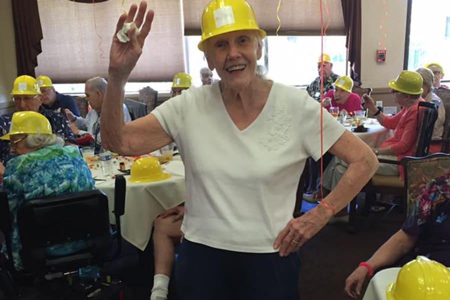 Resident waving to the camera at the dining room construction kick-off party at Bella Vista Senior Living in Mesa, Arizona