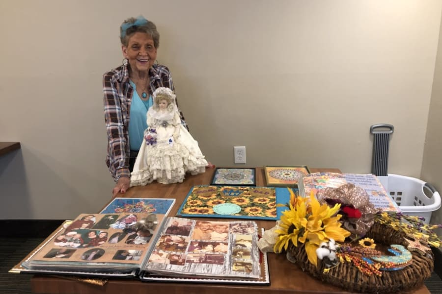 Resident posing with her doll and photo albums at the show and tell crafts event at Bella Vista Senior Living in Mesa, Arizona