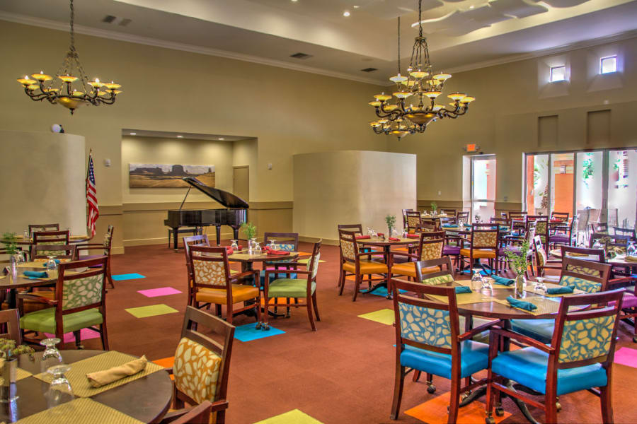 Chandeliers and colorful carpet in the dining hall at Casa Del Rio Senior Living in Peoria, Arizona