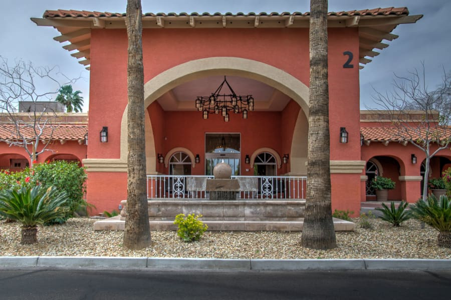 Exterior view of the building facade and landscaping at the entrance to Casa Del Rio Senior Living in Peoria, Arizona