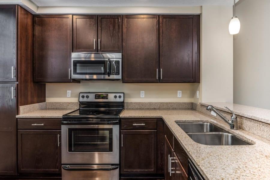 Dark wood cabinetry in a model senior apartment's kitchen at Riverwalk Pointe in Jupiter, Florida