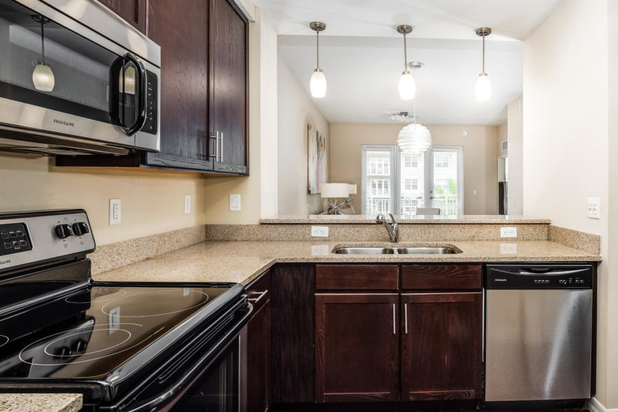 Granite countertops and custom lighting in a model senior apartment's kitchen at Riverwalk Pointe in Jupiter, Florida