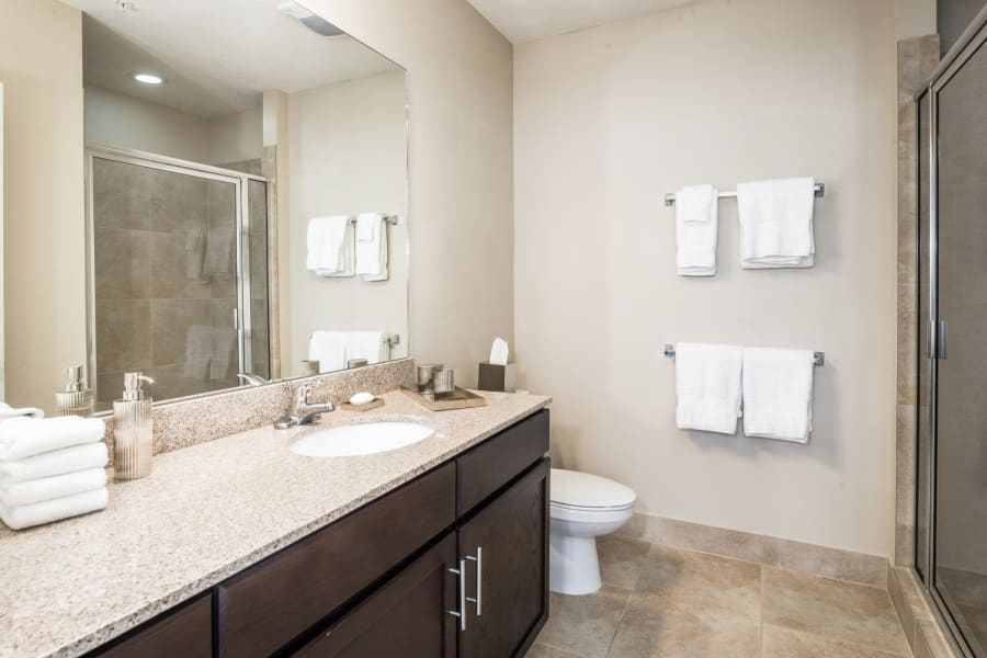 Spacious bathroom with a large vanity mirror and granite countertop in a model senior apartment at Riverwalk Pointe in Jupiter, Florida