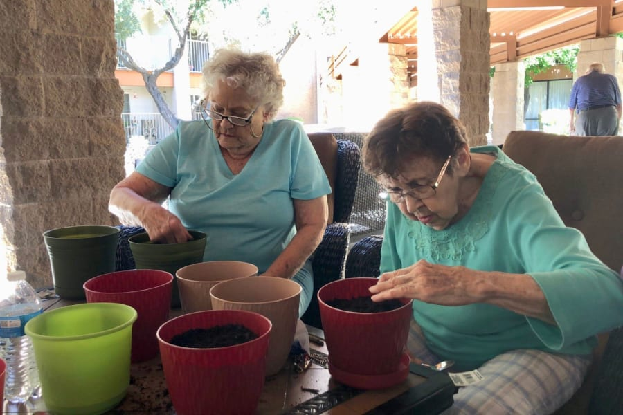 Residents planting flowers on Earth Day at Bella Vista Senior Living in Mesa, Arizona