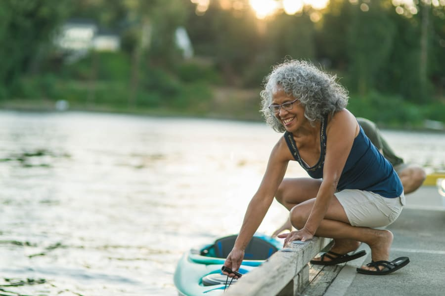 A woman by a lake getting into a kayak near Applewood Pointe of Westminster in Westminster, Colorado.