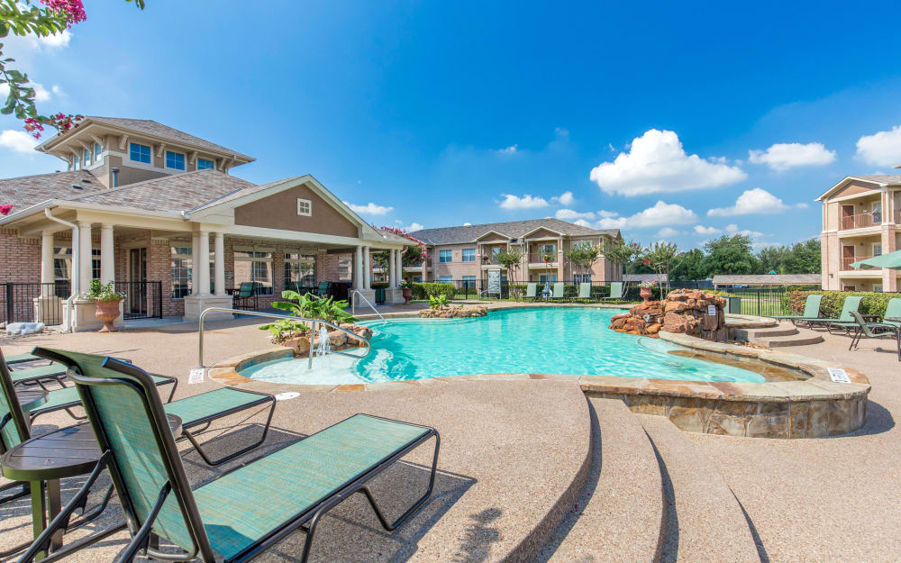 Swimming pool with a fountain on a sunny day at Ranch at Hudson Xing in McKinney, Texas