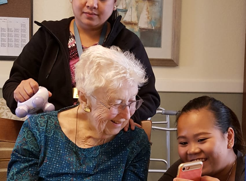 Resident and young girl looking at smart phone at Peninsula Reflections in Colma