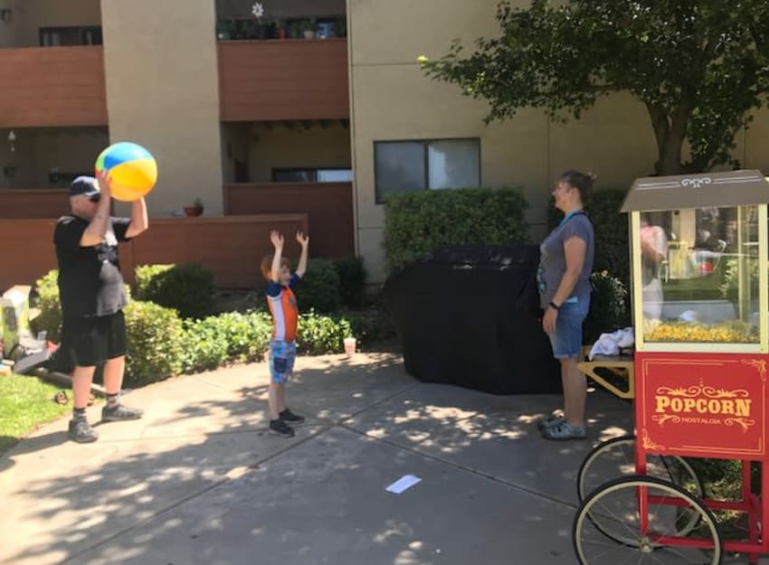 Family tossing a beach ball at Golden Pond Retirement Community