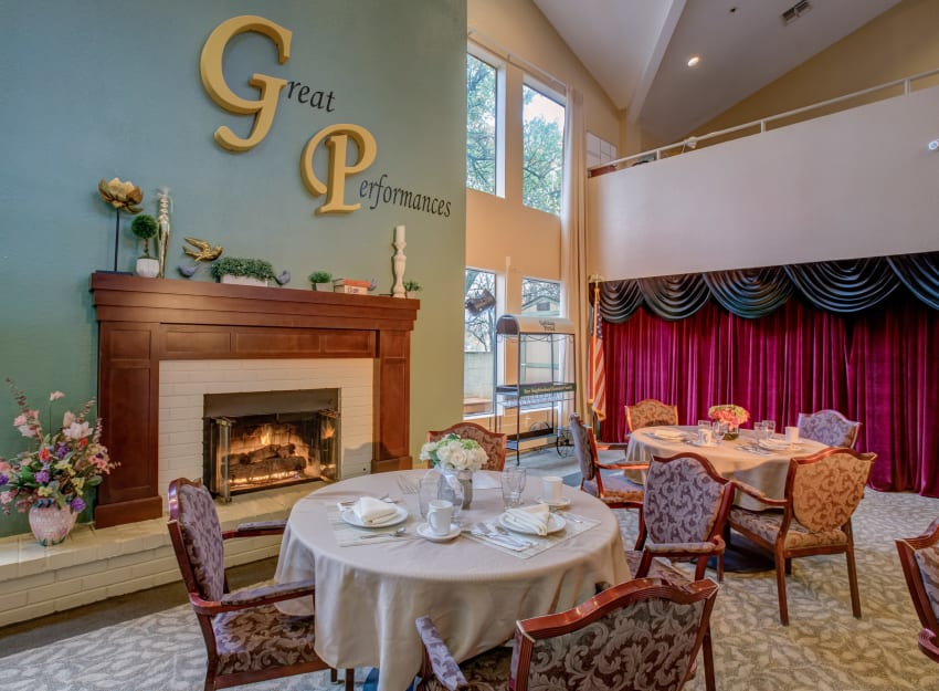 Quaint dining room with a fireplace at Golden Pond Retirement Community in Sacramento, California