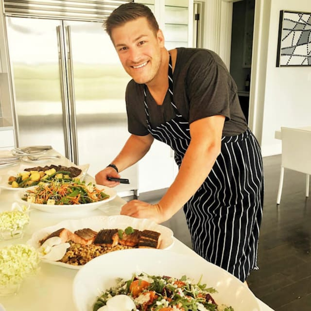 Man posing in kitchen with prepped meals