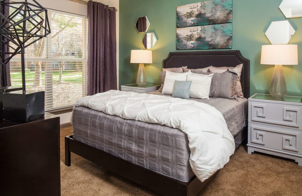 Well-decorated master bedroom with bay windows in model home at Presley Oaks in Charlotte, North Carolina