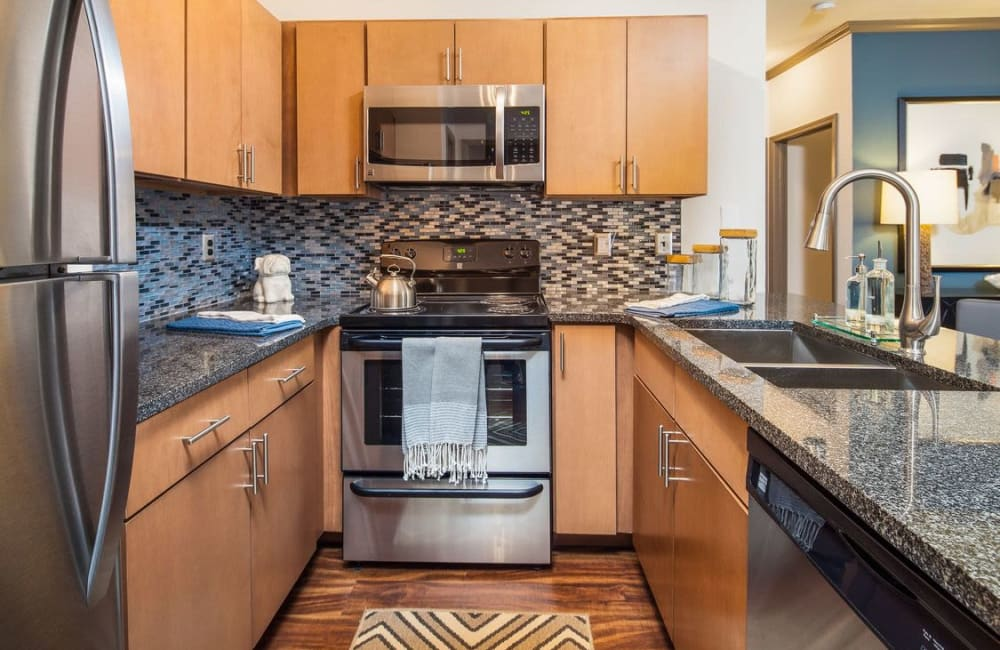 Hardwood floor and stainless-steel appliances in model home's kitchen at Presley Oaks in Charlotte, North Carolina