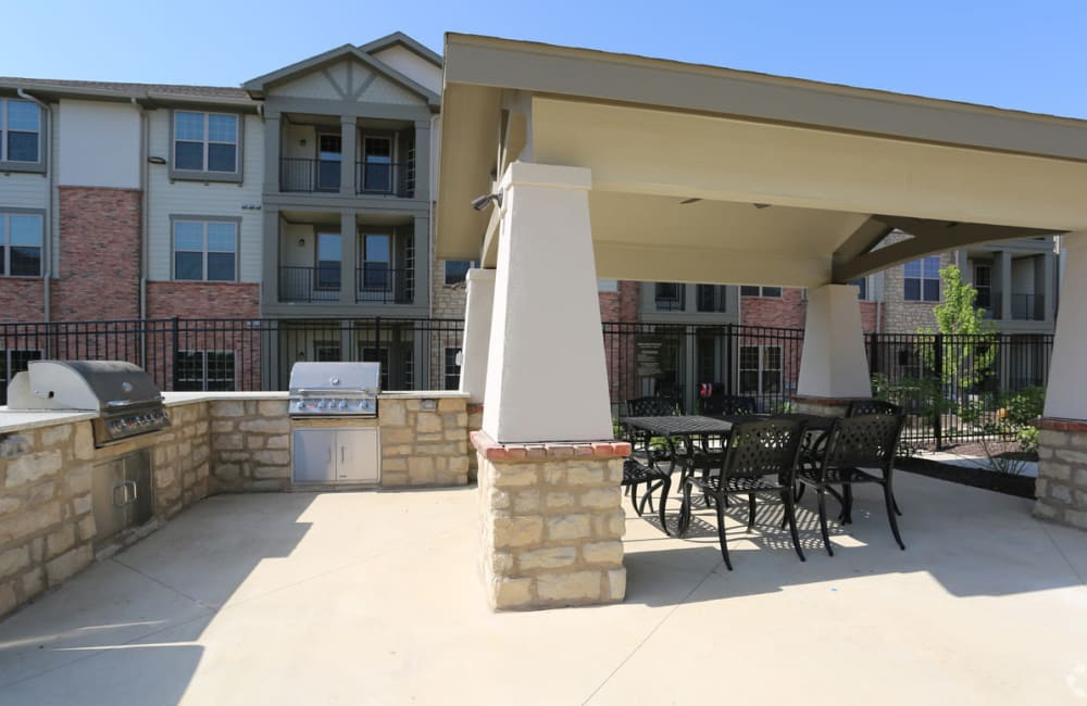 An outdoor grilling area with an outdoor dining table at Boulders at Overland Park Apartments in Overland Park, Kansas