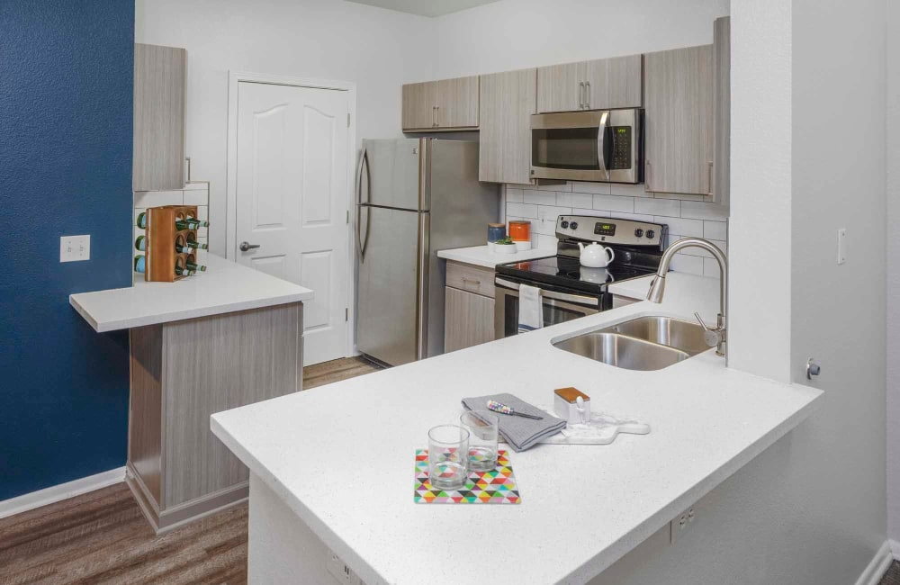 A kitchen with an island and hardwood floors at The Grove at Orenco Station in Hillsboro, Oregon