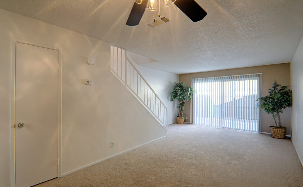 Spacious, open floor plan with ceiling fan in model home at Woodlands West Apartment Homes in Lancaster, CA