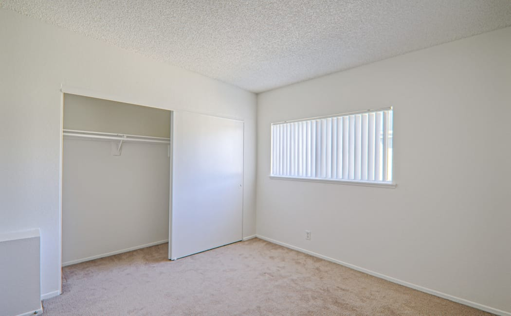 Large bedroom with plenty of space to make it your own at Woodlands West Apartment Homes in Lancaster, CA