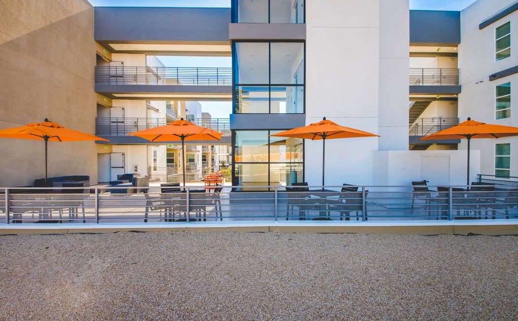 View of rooftop patio with community buildings in the background at IMT Sherman Circle in Van Nuys, CA