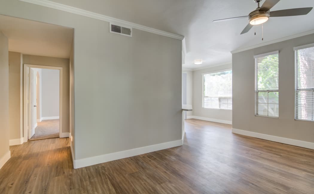 Hardwood floors and ceiling fans in the open-concept floor plan of an apartment home at Lumiere Chandler in Chandler, Arizona