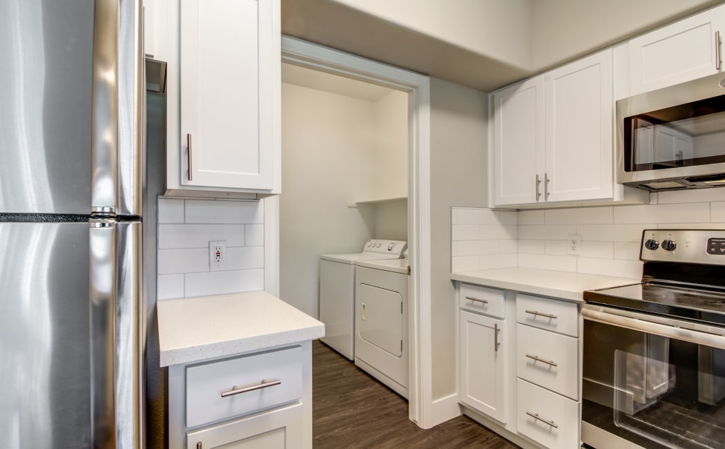 Modern kitchen and the adjacent laundry room in an apartment home at Lumiere Chandler in Chandler, Arizona