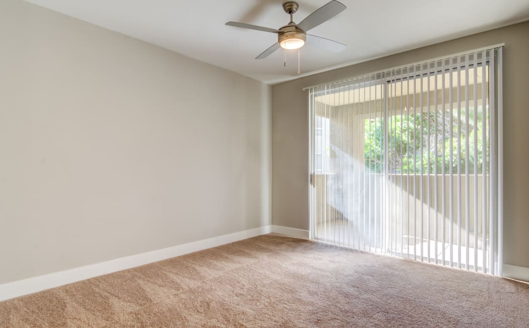 Plush carpet and a ceiling fan in an apartment home's bedroom at Lumiere Chandler in Chandler, Arizona