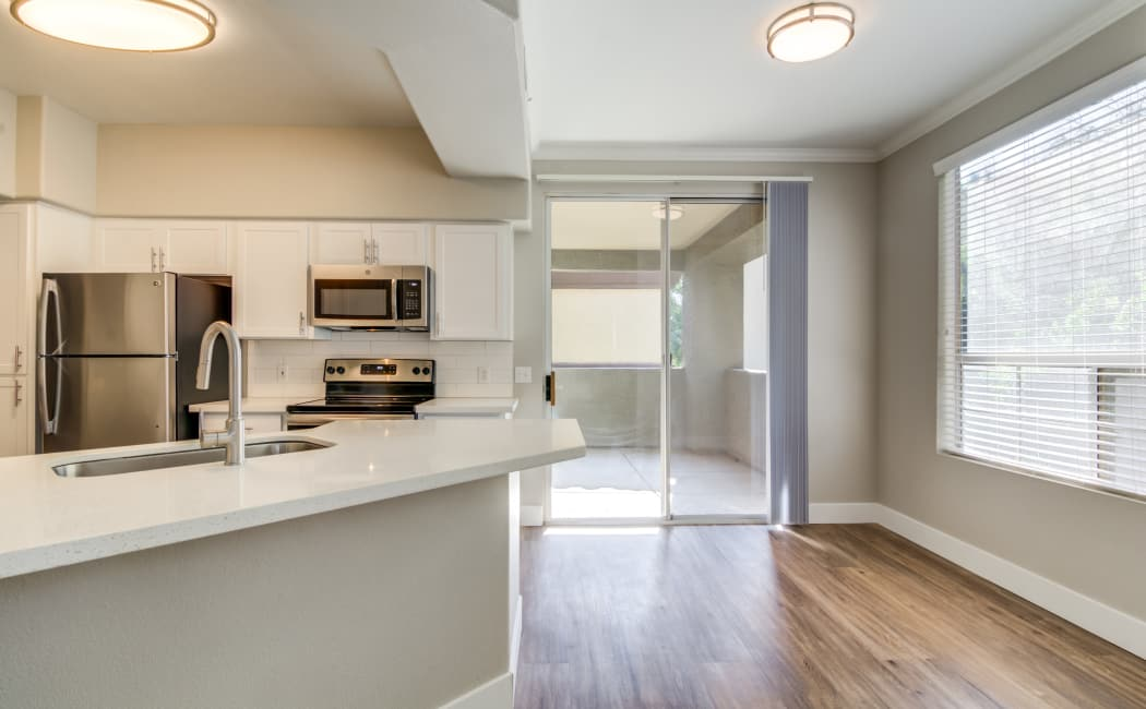 Kitchen and hallway with hardwood floors in apartment home at Lumiere Chandler in Chandler, Arizona