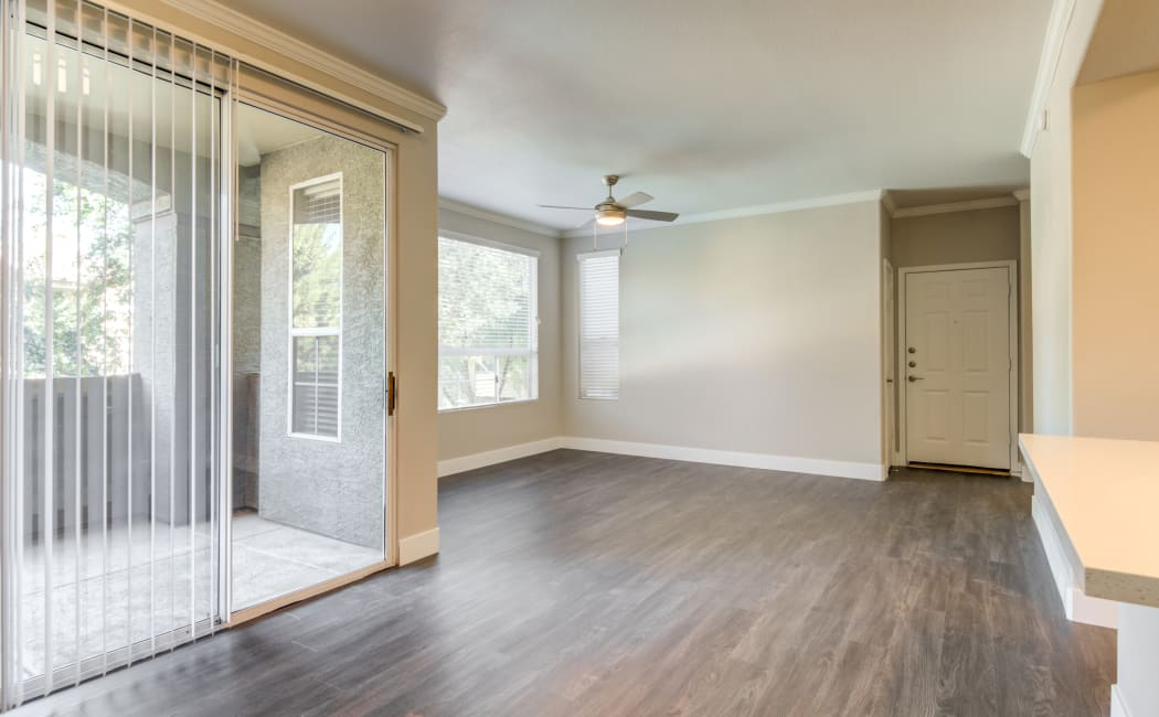 Hardwood floors and a sliding door to the private balcony of an apartment home at Lumiere Chandler in Chandler, Arizona