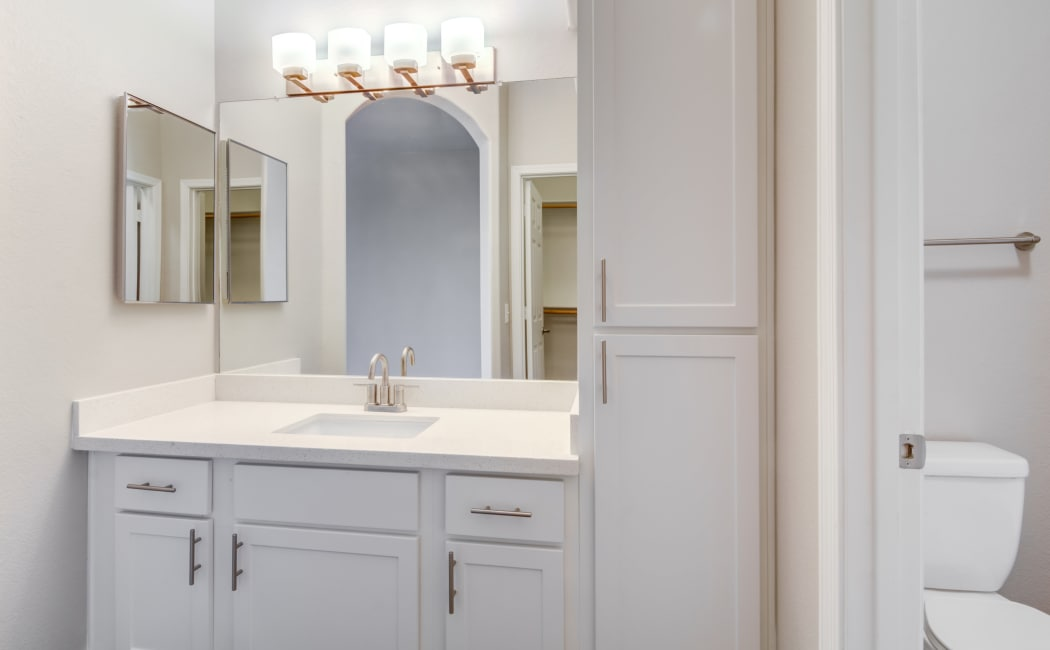 Well-lit bathroom with large vanity mirror in apartment home at Lumiere Chandler in Chandler, Arizona