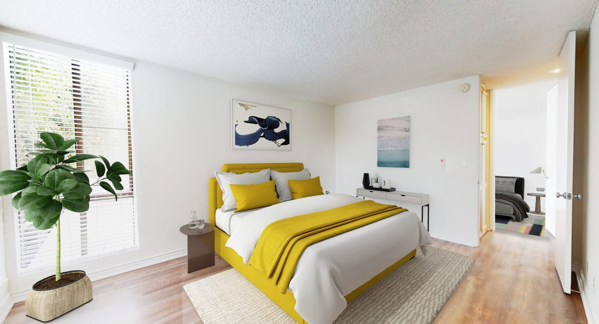Hardwood flooring and ample natural light in a model home's bedroom at Mariners Village in Marina del Rey, California