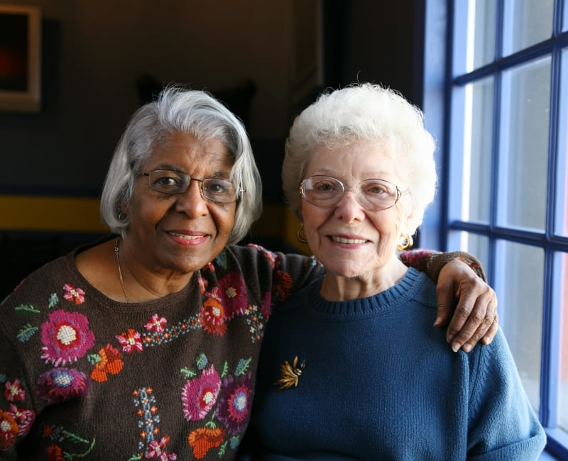 Resident friends put their arms around each other at The Sanctuary at St. Cloud in St. Cloud, Minnesota
