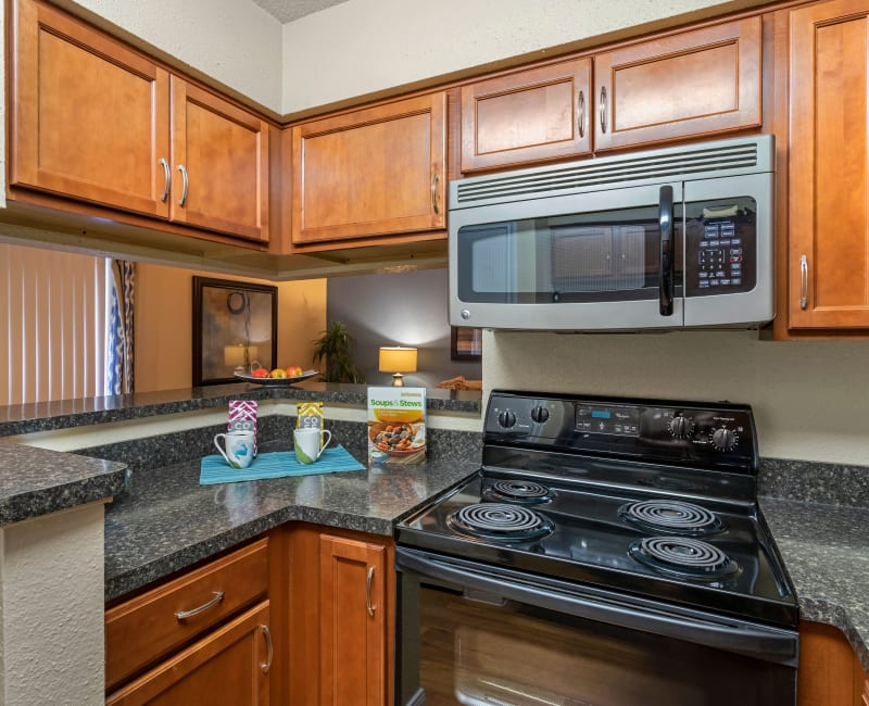Model kitchen with built-in microwave and custom cabinetry at Foundations at River Crest & Lions Head in Sugar Land, Texas
