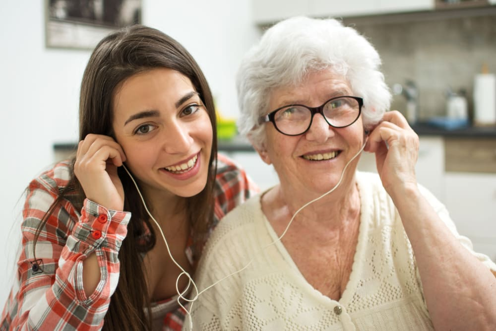 Grandmother and granddaughter sharing earbuds at Cottagewood Senior Communities