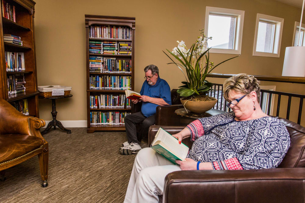 Residents enjoy a good novel in the library at Solana at The Park