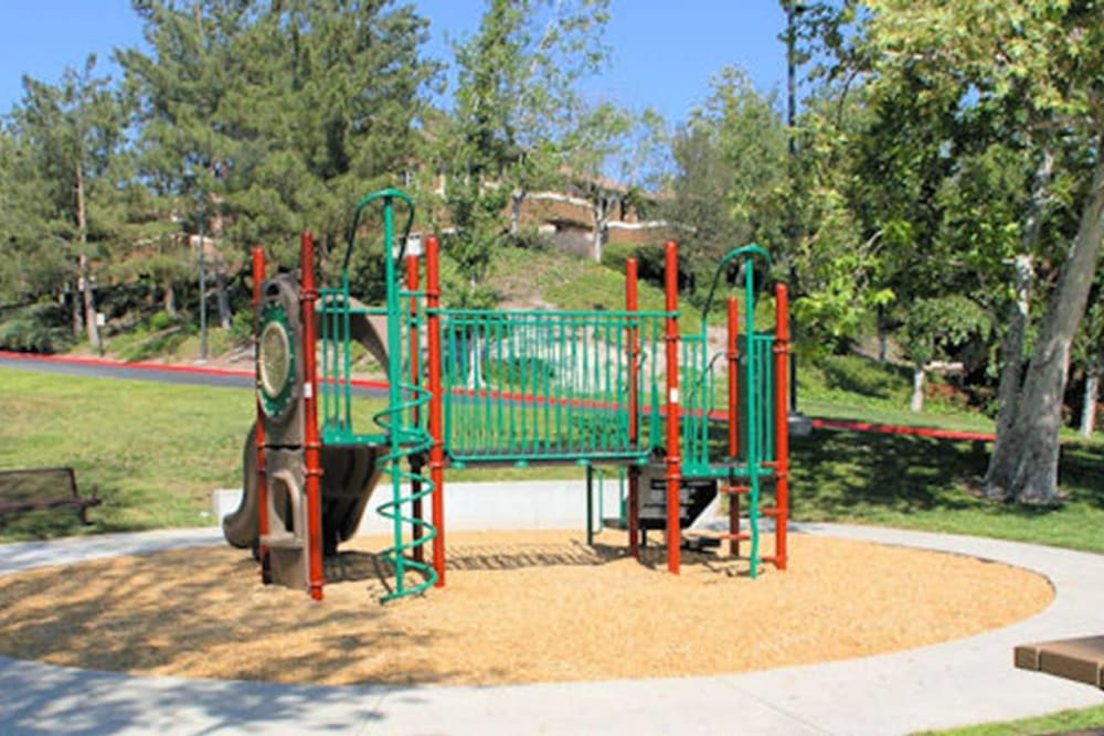 Onsite playground with a slide at Paloma Summit Condominium Rentals in Foothill Ranch, California