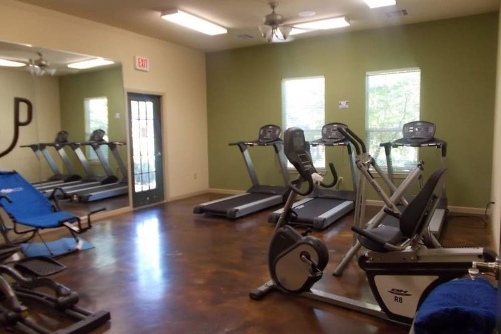 A fitness center with individual workout stations at Woodside Manor in Conroe, Texas