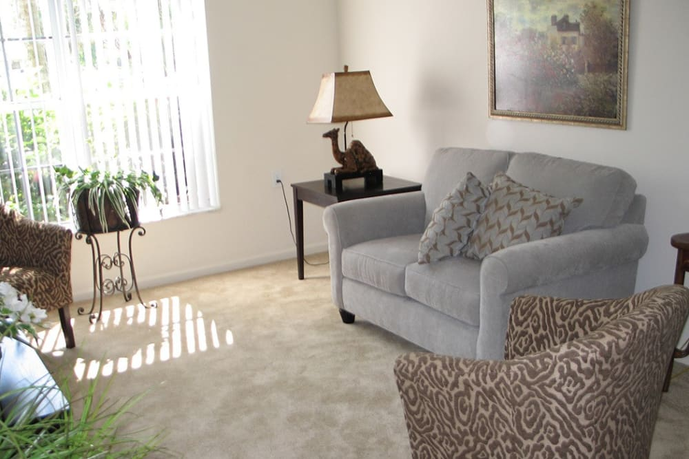 Living room model with grey chair at Grand Villa of Delray West in Florida