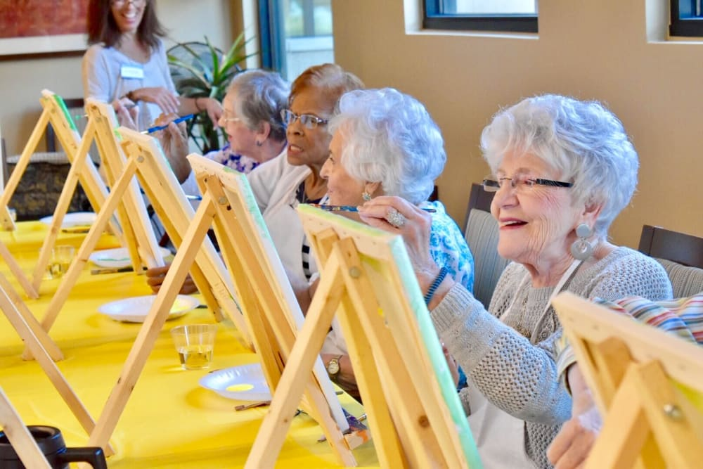 Active living residents painting sunflowers at Merrill Gardens at Anthem