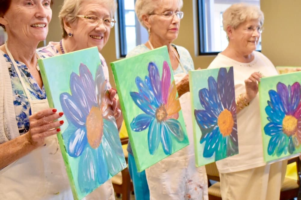Active living residents showing sunflower paintings at Merrill Gardens at Anthem