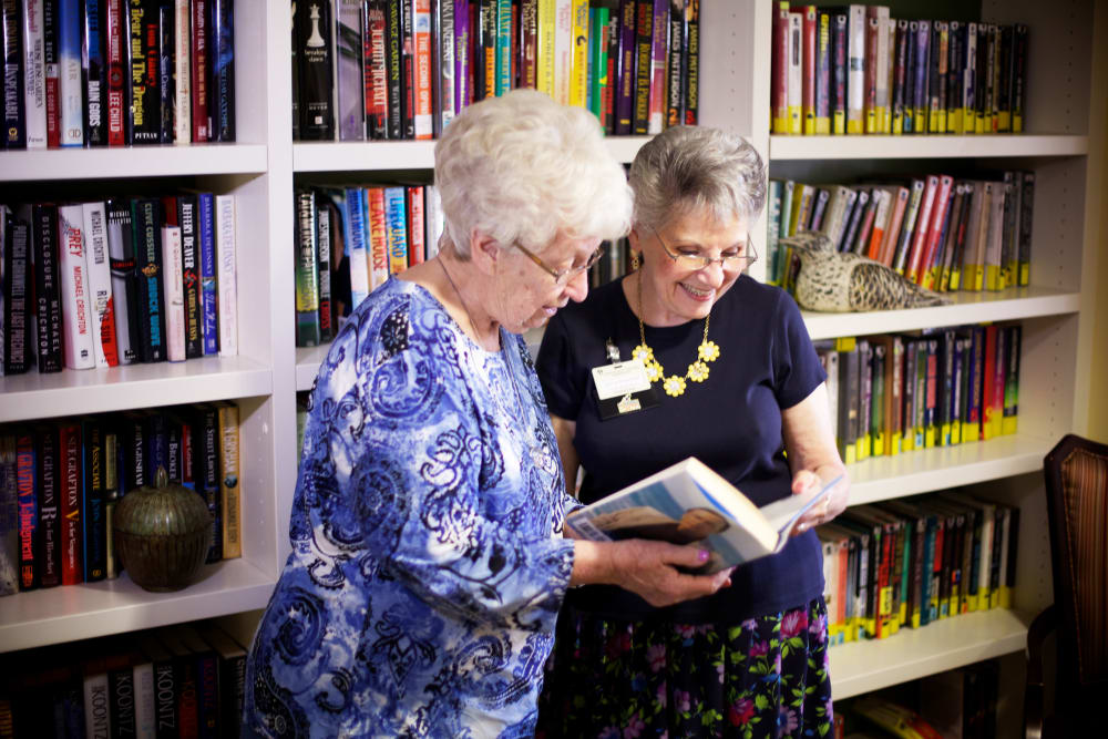 Residents enjoy reading books in the library at Someren Glen