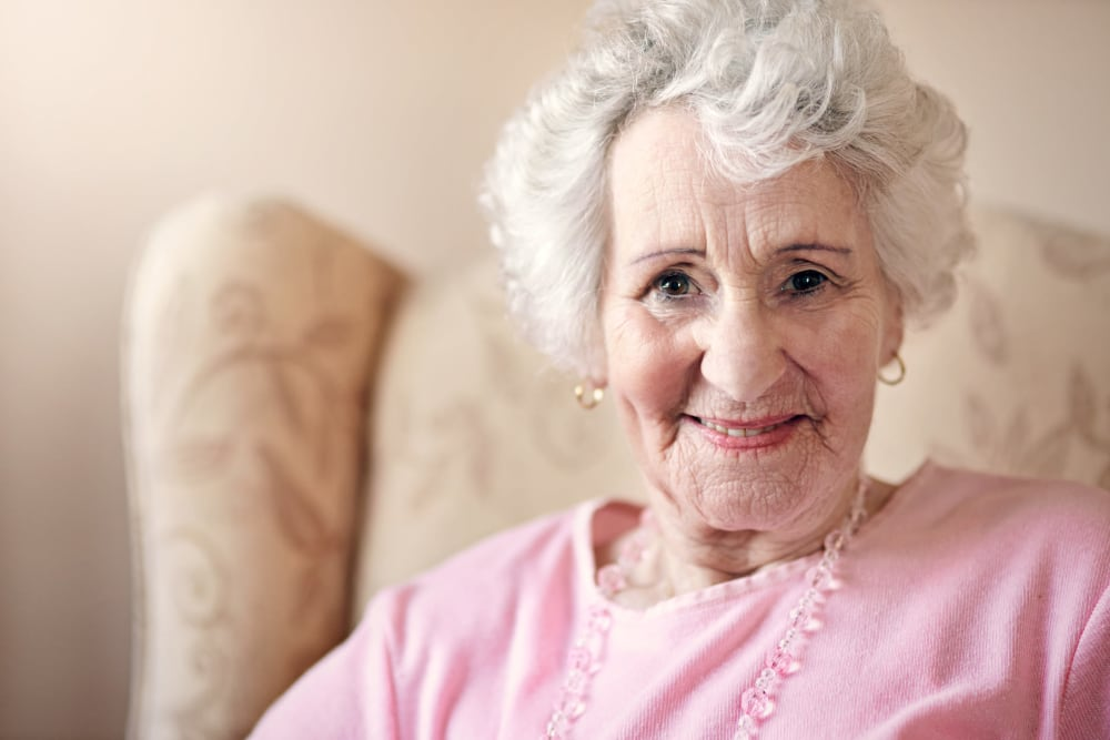A Oakleaf Senior Living resident smiles for her photo to be taken.