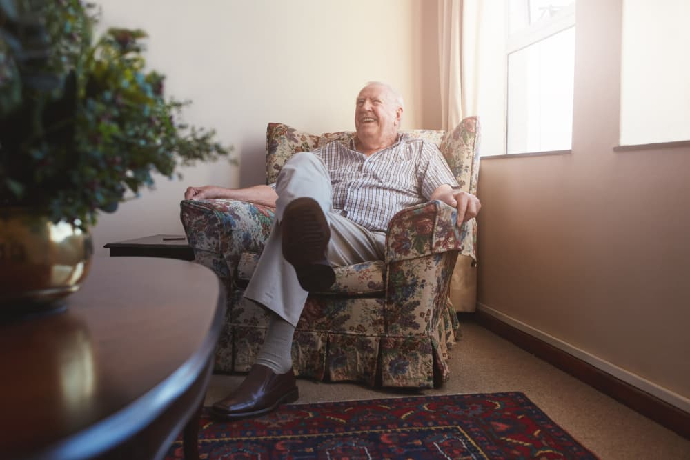 An elderly man sits in a comfy recliner in his apartment at Oak Park Villages Senior Living
