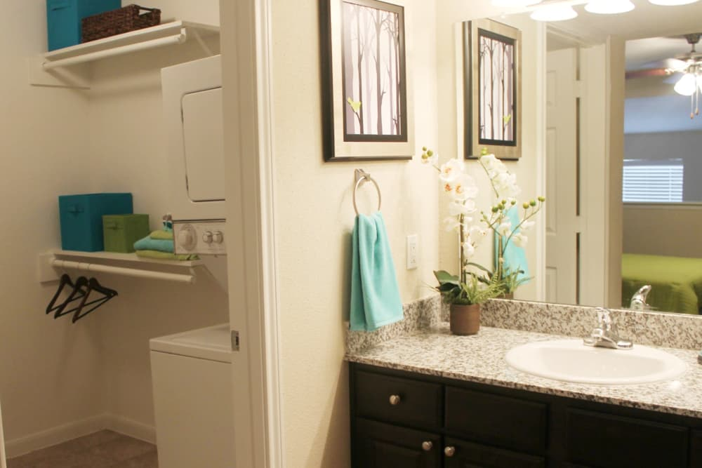 Washer/dryer and bathroom at The Abbey at Montgomery Park apartments in Conroe